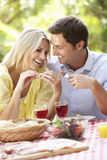 Pares que disfrutan de la comida al aire libre junto Imagenes de archivo