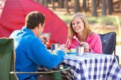 Pares que disfrutan de la comida en acampada Imagen de archivo