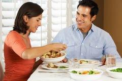 Pares que disfrutan de la comida en casa Imágenes de archivo libres de regalías