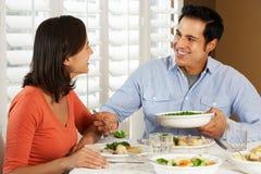 Pares que disfrutan de la comida en casa Foto de archivo