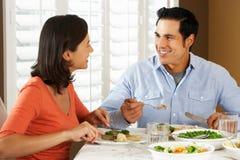 Pares que disfrutan de la comida en casa Fotografía de archivo libre de regalías