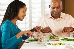 Pares que disfrutan de la comida en casa Fotografía de archivo