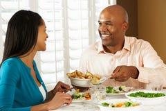 Pares que disfrutan de la comida en casa Imagenes de archivo