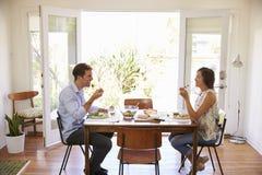 Pares que disfrutan de la comida en casa junto Imágenes de archivo libres de regalías