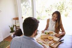 Pares que disfrutan de la comida en casa junto Fotografía de archivo