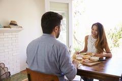 Pares que disfrutan de la comida en casa junto Imagenes de archivo