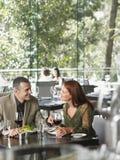 Pares que disfrutan de la comida en el restaurante Fotografía de archivo libre de regalías