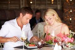 Pares que disfrutan de la comida en restaurante Imagen de archivo