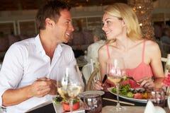 Pares que disfrutan de la comida en restaurante Fotografía de archivo libre de regalías