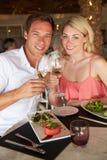 Pares que disfrutan de la comida en restaurante Foto de archivo libre de regalías