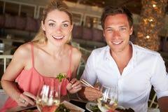 Pares que disfrutan de la comida en restaurante Imágenes de archivo libres de regalías