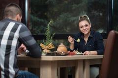 Pares que disfrutan de la comida en restaurante Fotos de archivo libres de regalías