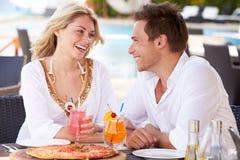 Pares que disfrutan de la comida en restaurante al aire libre Fotografía de archivo libre de regalías