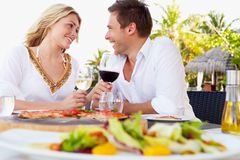 Pares que disfrutan de la comida en restaurante al aire libre Imagen de archivo libre de regalías