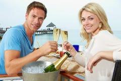 Pares que disfrutan de la comida en restaurante de la orilla del mar Imagen de archivo libre de regalías