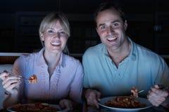 Pares que disfrutan de la comida mientras que ve la TV Imagen de archivo libre de regalías