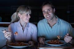 Pares que disfrutan de la comida mientras que ve la TV Foto de archivo