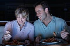 Pares que disfrutan de la comida mientras que ve la TV Foto de archivo libre de regalías