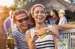 Pares que disfrutan de la comida y de bebidas en el partido Imagen de archivo libre de regalías