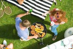Pares que disfrutan de la fiesta de jardín de la barbacoa Imagen de archivo