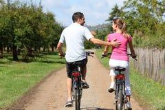 Pares que disfrutan de paseo de la bici Imagen de archivo libre de regalías