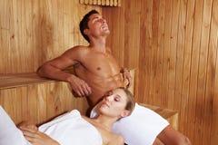 Pares que disfrutan de paz en sauna Foto de archivo