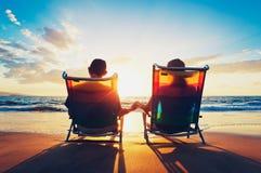 Pares que disfrutan de puesta del sol en la playa Foto de archivo