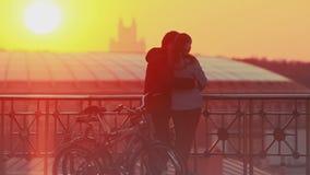 Pares que disfrutan de puesta del sol escénica en la ciudad metrajes