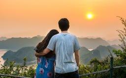 Pares que disfrutan de puesta del sol romántica en el punto de vista Imagen de archivo libre de regalías