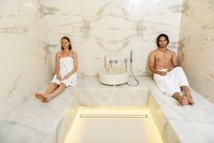 Pares que disfrutan de sauna caliente Imagen de archivo