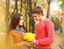 Pares que disfrutan de temporada de otoño de oro del otoño Imagen de archivo libre de regalías