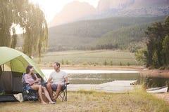 Pares que disfrutan de vacaciones que acampan por el lago que hace una tostada imagen de archivo