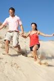 Pares que disfrutan del día de fiesta de la playa que se ejecuta abajo de la duna Fotografía de archivo