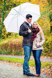 Pares que disfrutan del día de la caída que tiene paseo a pesar de la lluvia Imagenes de archivo