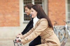 Pares que dão um ciclo na cidade Fotografia de Stock Royalty Free