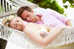Pares que dormem na rede da praia Fotografia de Stock