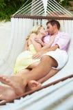 Pares que dormem na rede da praia Foto de Stock Royalty Free