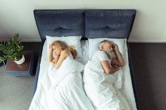 Pares que duermen de nuevo a la parte posterior en cama Foto de archivo