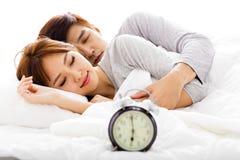 pares que duermen en cama al lado de un despertador Imágenes de archivo libres de regalías