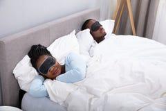 Pares que duermen en cama usando m?scara de ojo fotografía de archivo libre de regalías