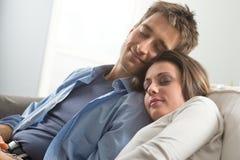 Pares que duermen en el sofá imagen de archivo