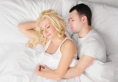 Pares que duermen en una cama Foto de archivo