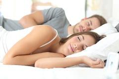 Pares que duermen en una cama cómoda