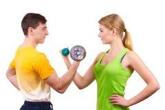 Pares que ejercitan con las pesas de gimnasia que levantan pesos Imagen de archivo libre de regalías