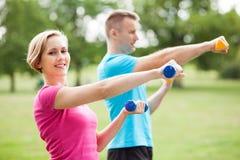 Pares que ejercitan con pesas de gimnasia Foto de archivo