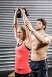Pares que ejercitan con pesas de gimnasia Fotografía de archivo libre de regalías