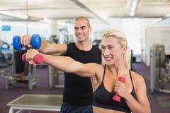 Pares que ejercitan con pesas de gimnasia en gimnasio Imagenes de archivo
