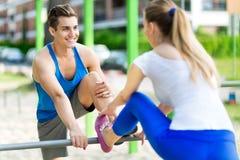 Pares que ejercitan en el gimnasio al aire libre Imagen de archivo libre de regalías