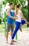 Pares que ejercitan en el gimnasio al aire libre Imagenes de archivo