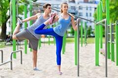 Pares que ejercitan en el gimnasio al aire libre Imagen de archivo